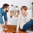 Couple Trying To Close Suitcase At Home — Stock Photo