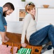 Couple Trying To Close Suitcase At Home — Stock Photo #26744297