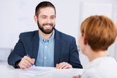 Man Explaining Documents To Female Co worker At Desk — Stock Photo