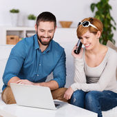 Young Couple Using Laptop And Talking On Phone — Stock Photo