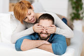 Woman Covering Mans Eyes While Lying On Sofa — Stock Photo