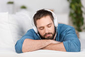Young Man Lying On Sofa While Listening To Music — Stock Photo