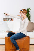 Woman With Map Pointing While Sitting On Suitcase — Stockfoto