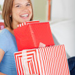 Stock Photo: Smiling woman with a pile of gifts