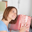 Smiling woman shaking her gift — Stock Photo