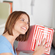 Stock Photo: Smiling womshaking her gift