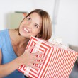 Pretty woman shaking a large present — Stock Photo