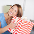 Stock Photo: Pretty woman shaking a large present