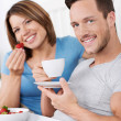 Relaxing couple enjoying breakfast in bed — Stock Photo