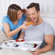 Laughing couple enjoying breakfast in bed — Stock Photo