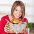 Smiling woman with golden fresh baked croissants — Stock Photo #26808197