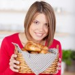 Smiling woman with golden fresh baked croissants — Stock Photo