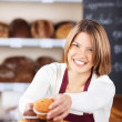 Pretty smiling worker selecting muffins — Stock Photo