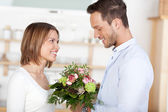 Young man gives flowers to girl — Stock Photo