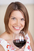 Smiling woman with a glass of red wine — Stock Photo