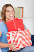 Smiling woman with a pile of gifts — Stock Photo