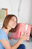 Smiling woman shaking her gift — Stockfoto
