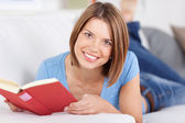 Happy young woman enjoying a book — Stock Photo