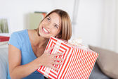 Pretty woman shaking a large present — Foto de Stock