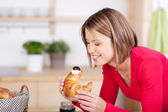 Woman having a croissant for breakfast — Stockfoto