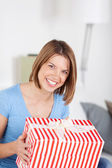 Excited woman with a large striped gift — Stock Photo