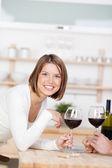 Portrait of a beautiful blond woman drinking wine — Stock Photo