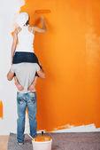 Couple having fun painting a wall — Stock Photo