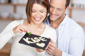 Smiling couple holding a stone slab with cheese — Stock Photo