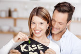 Young couple holding a stone slab with cheese — Stock Photo