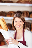 Happy bakery worker with baguettes — Stock Photo