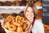Smiling bakery assistant with assorted rolls — Stock Photo