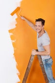 Man is painting with orange color — Stock Photo