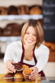 Bakery worker sorting the muffins — Stock Photo