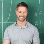 Teacher Using Digital Tablet Against Chalkboard — Stock Photo #26818059