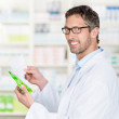 Pharmacist Holding Prescription Paper And Product In Pharmacy — Stock Photo