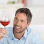 Smiling Mature Man Looking At Wineglass At Home — Stock Photo