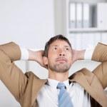 επιχειρηματίας με τα χέρια πίσω από το κεφάλι να κοιτάζει στο γραφείο — Φωτογραφία Αρχείου