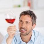 Mature Man Looking At Wineglass At Home — Stock Photo #26819743