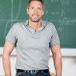 Mature Teacher Leaning On Bench In Classroom — Stock Photo