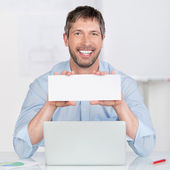Businessman Holding Blank Sign At Office Desk — Stock Photo