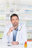 Male Pharmacist Holding Glasses At Pharmacy Counter — Stock Photo