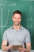 Učitel pomocí digitálních tabletu proti tabuli — Stock fotografie