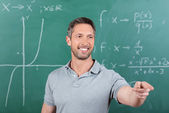Teacher Pointing While Looking Away Against Chalkboard — Stock Photo