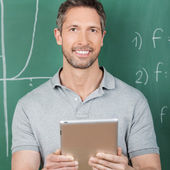 Male Teacher Holding Digital Tablet Against Chalkboard — Stock Photo