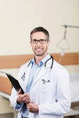 Smiling Doctor With Clipboard In Hospital — Stock Photo