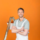 Smiling Painter With Arms Crossed Standing Against Orange Painted Wall — Stock Photo