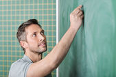 Teacher Writing With Chalk On Board In Classroom — Stock Photo