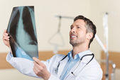 Mature Doctor Looking At X-Ray Report In Hospital — Stock Photo