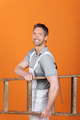 Smiling Painter Carrying Wooden Ladder Against Orange Painted Wall — Stock Photo
