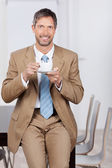 Smiling Businessman Having Coffee While Leaning On Desk — Stock Photo